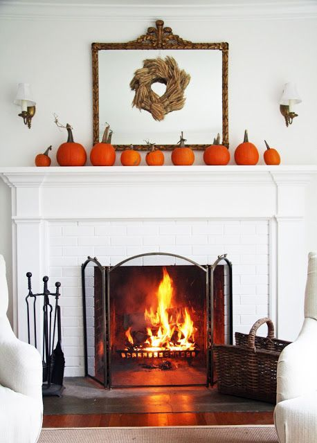 a simple rustic mantel with an arrangement of orange pumpkins and a wheat wreath on the mirror