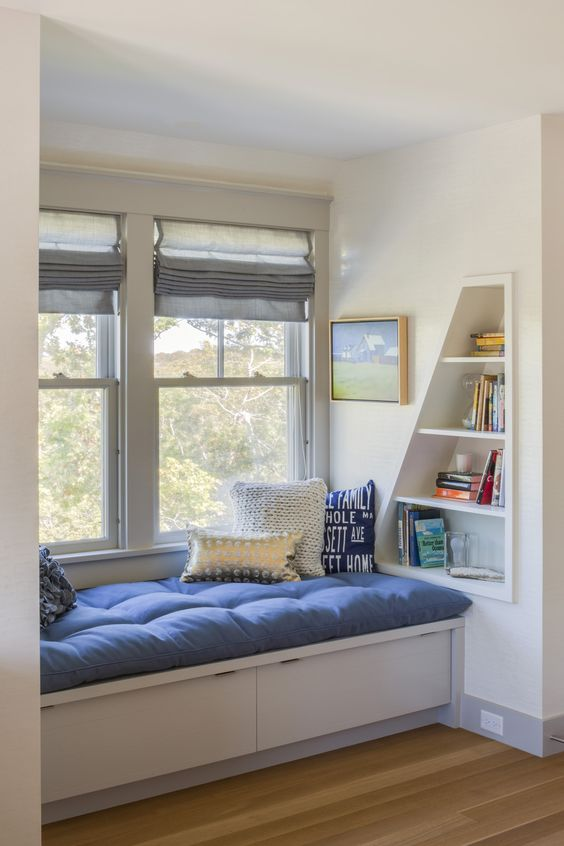a small coastal reading nook with an uholstered bench with pillows and little geometric built-in shelves