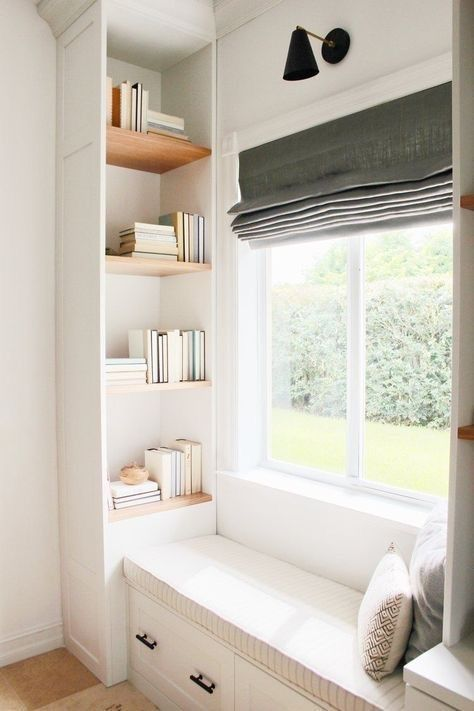a small contemporary reading nook by the window, with built-in bookshelves and dark shades is a veyr cozy space