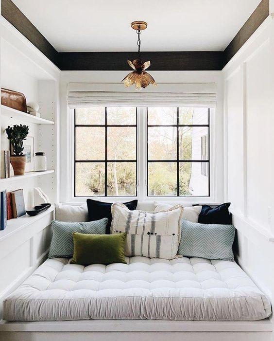 a small contemporary reading nook by the window, with soem shelves built in and colorful pillows
