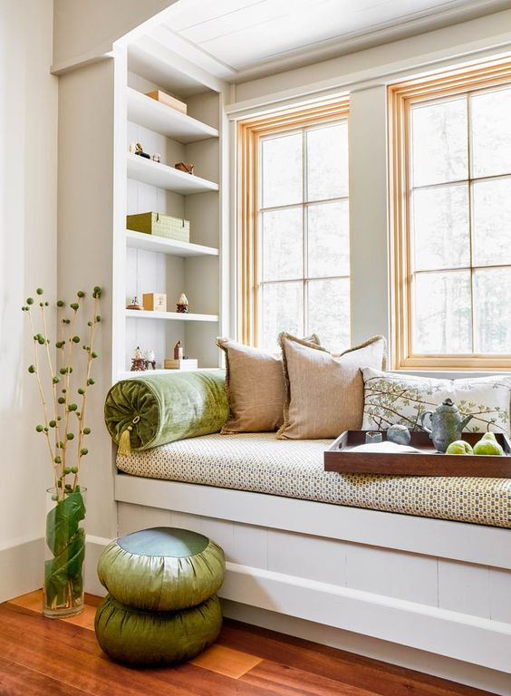 a small windowsill reading nook with bright pillows and built-in shelves looks super cozy and fresh