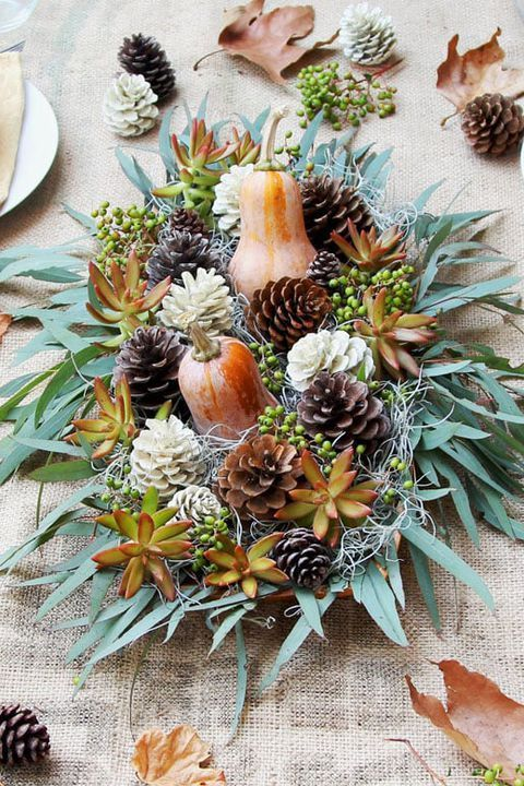 a stylish Thanksgiving centerpiece of a wooden bowl with greenery, succulents, pinecones, gourds, berries is a rustic arrangement