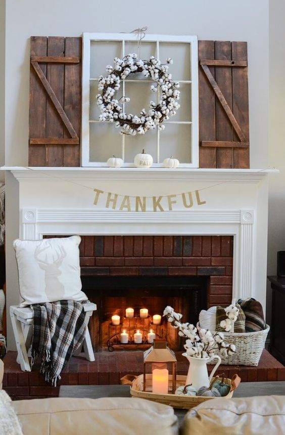 a stylish Thanksgiving mantel with white pumpkins, a cotton wreath and candles on a stand in the fireplace