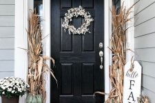 a stylish and casual fall porch with stacked heirloom pumpkins, corn husks, a floral wreath and potted blooms