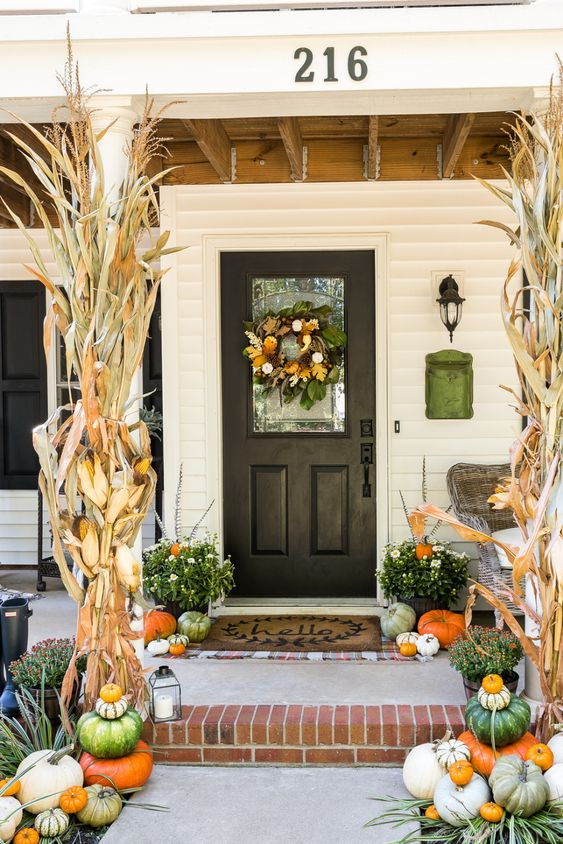 a stylish fall porch with corn husks, green, white and orange pumpkins, candle lanterns and a fresh fall wreath