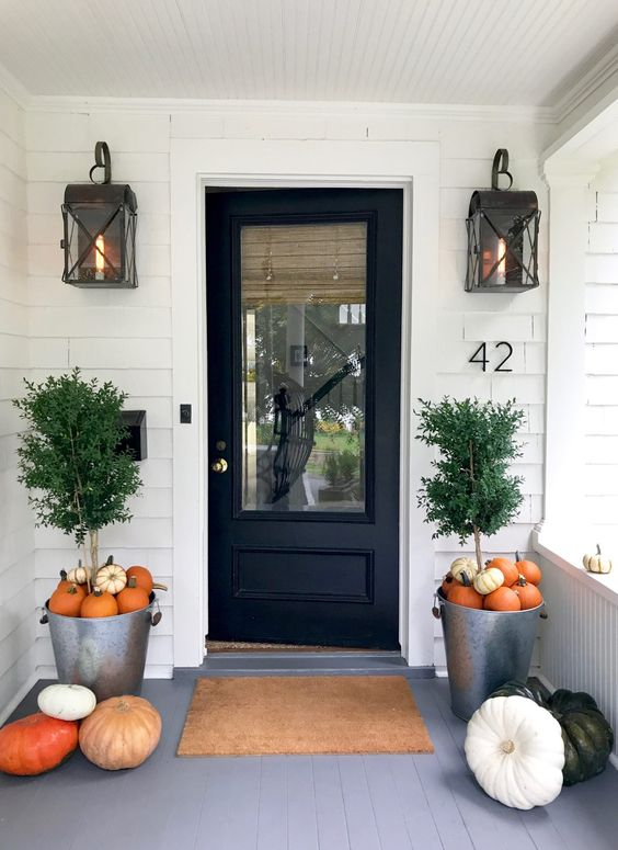 a stylish modern fall porch with trees in buckets covered with pumpkins and some more on the floor