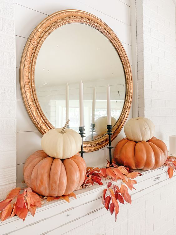a stylish vintage inspired mantel with bright leaves and stacked pumpkins plus a gold frame mirror
