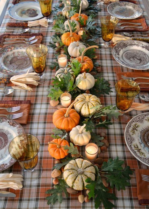 a traditional Thanksgiving centerpiece of oak leaves and acorns, candles and faux and natural pumpkins