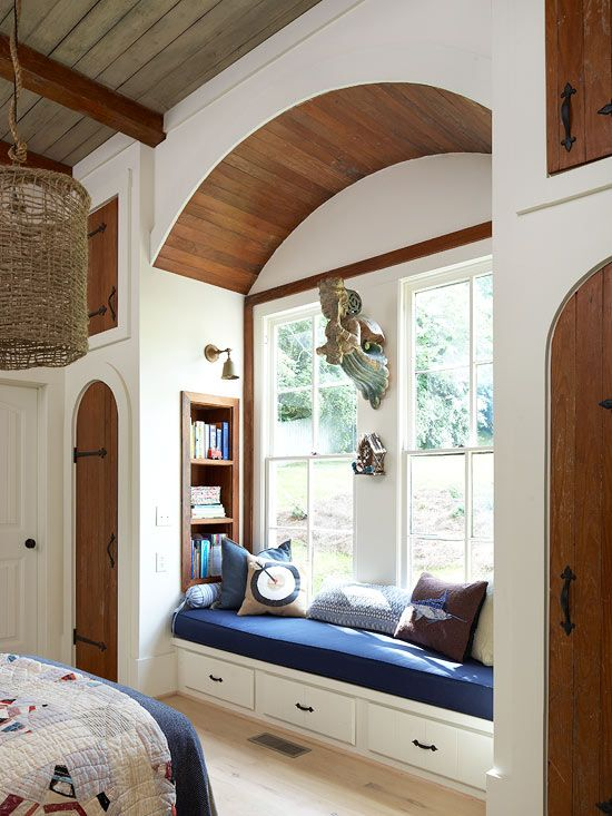 a traditional windowsill reading space with an upholstered bench with drawers and built-in stained bookshelves