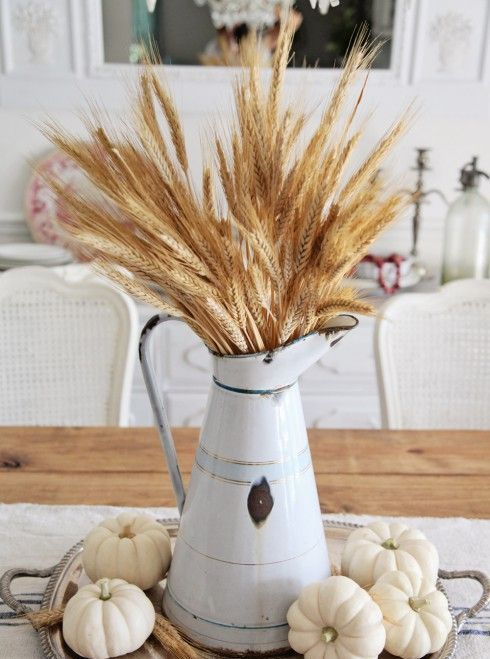 a very relaxed harvest centerpiece with white pumpkins and wheat in a vintage pitcher is a nice Thanksgiving idea