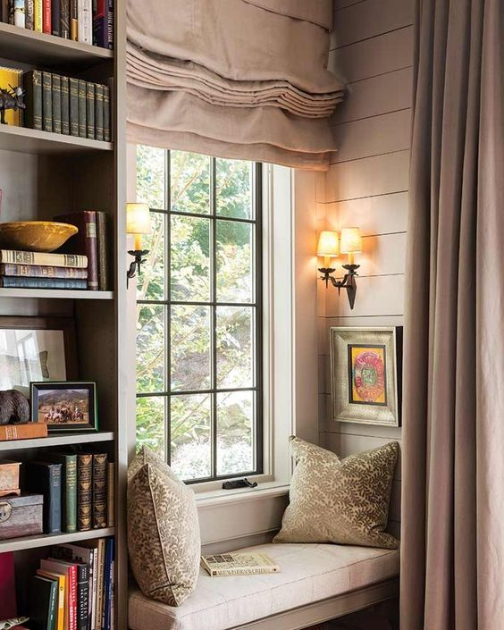 a vintage windowsill reading nook with a small upholstered bench, printed pillows and bookshelves next to it