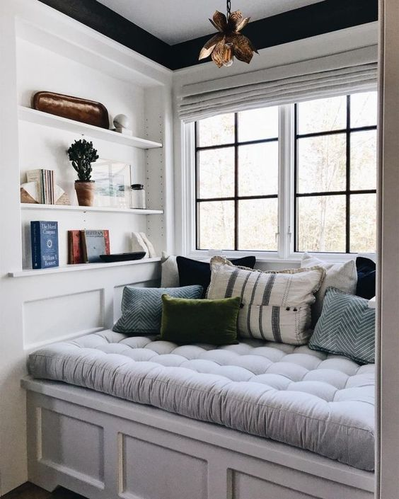 a welcomign and cozy reading nook by the window - a soft upholstered seat with drawers and some built-in shelves right here
