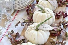 a wooden board with berries, leaves and white pumpkins with tags is a simple rustic centerpiece for the fall