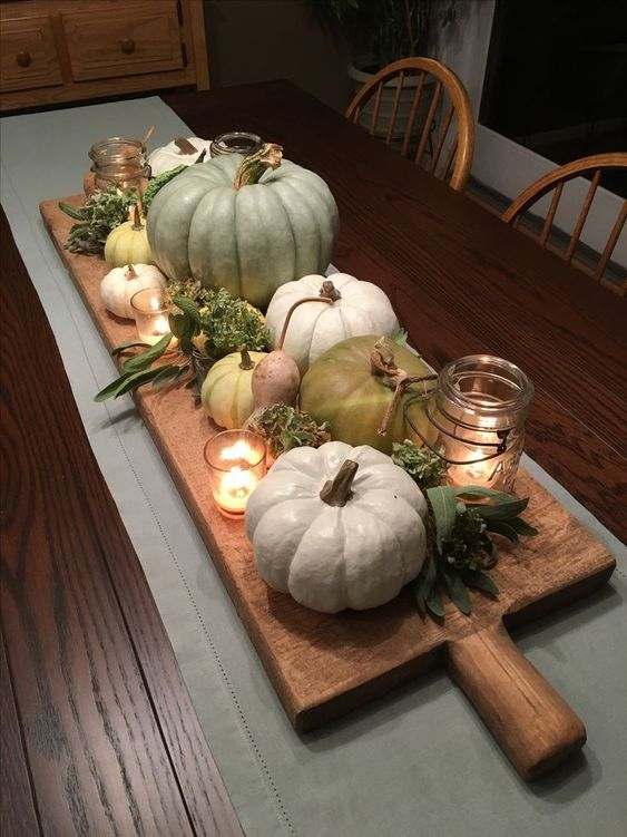 a wooden board with candles, greenery and green flowers, candles in candle lanterns and heirloom pumpkins