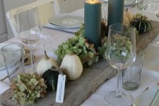 a wooden board with green hydrangeas, green candles, white pumpkins and gourds is a rustic Thanksgiving centerpiece