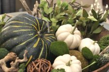a wooden bowl filled with leaves, gourds, pumpkins and moss is a beautiful natural centerpiece for the fall