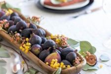 a wooden bowl with berries, figs and small blooms plus leaves around is a very lovely edible decoration