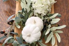 a wooden bowl with olive branches and leaves, white hydrangeas and pumpkins for Thanksgiving