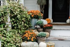 all-natural Thanksgiving porch decor with heirloom pumpkins, potted flowers and cabbages is very cute