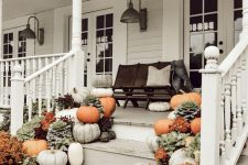 an all-natural fall porch with grey, white and orange pumpkins, bright orange potted blooms and a chalkboard sign