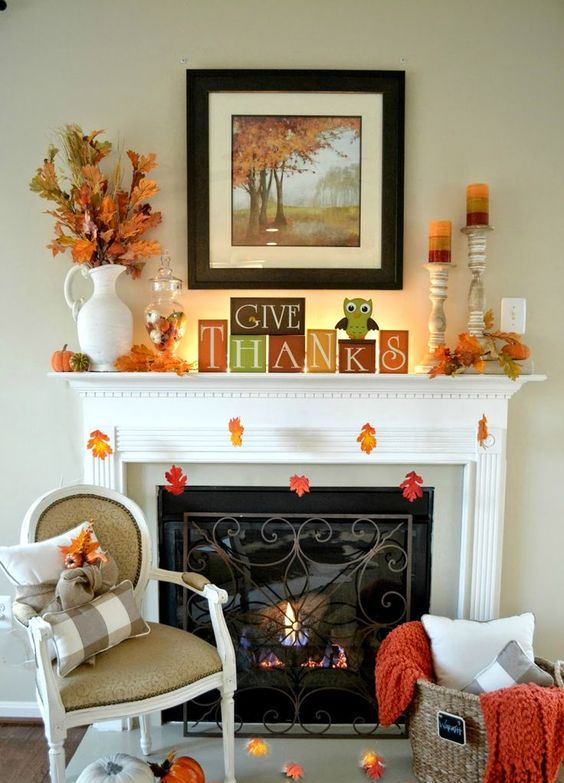 an easy and bright Thanksgiving mantel with bright cubes, colorful candles in candleholders, faux pumpkins and fall leaves