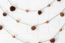 an easy and cool pinecone and wooden bead garland can be made for the fall and winter, it will add a woodland feel
