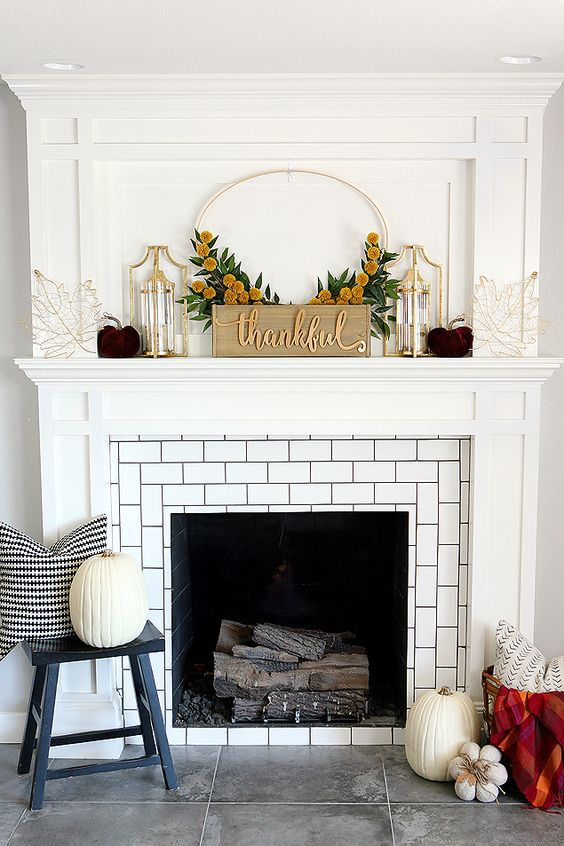 an elegant Thanksgiving mantel with purple velvet pumpkins, gold candle lanterns and wire leaves and a sign with a wreath
