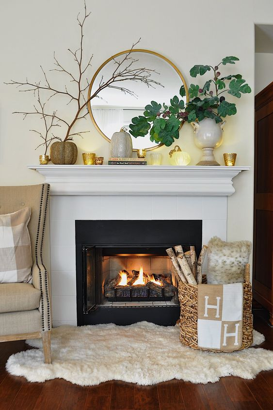 an elegant fall mantel with candles in candleholders, faux pumpkins and green leaves in a chic vase