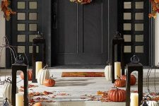 an elegant fall porch with pumpkins, leaves and candle lanterns, leaves and pumpkin wreath and a leaf garland