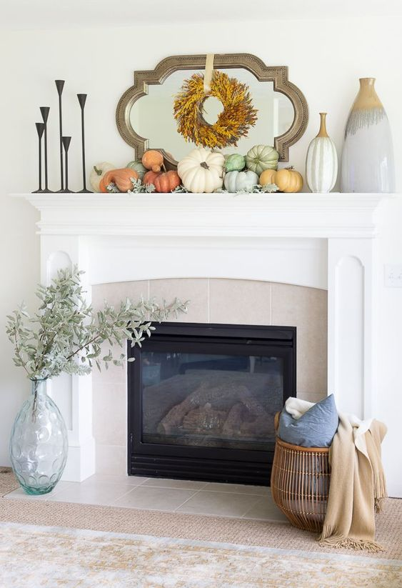 bright pumpkins and pale greenery, a wheat wreath and pale greenery in a vase next to the fireplace