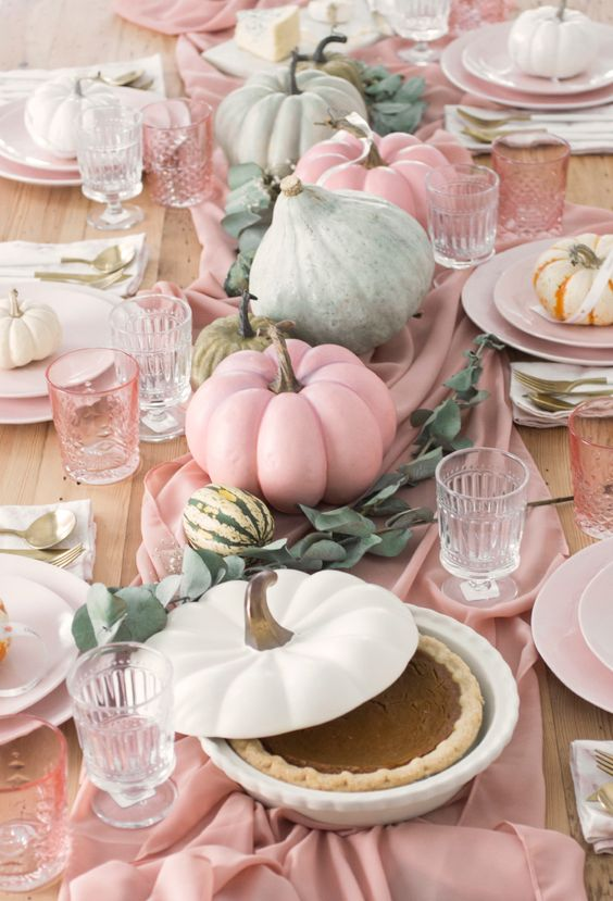 green and pink pumpkins with eucalyptus on a pink table runner make up a cool arrangement for the fall