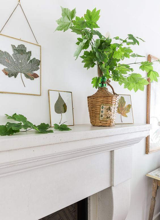minimalist but very natural Thanksgiving mantel decor with natural leaves in frames, green leaves in a bottle with a woven cover