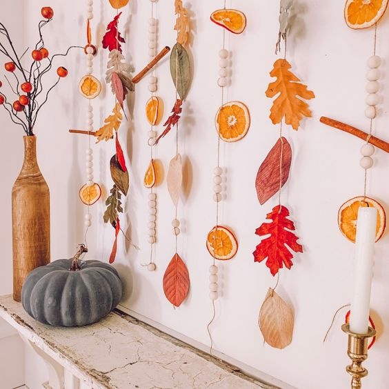 natural fall garlands with dried citrus slices, bright leaves, beads and cinnamon sticks are lovely for fall and Thanksgiving decor