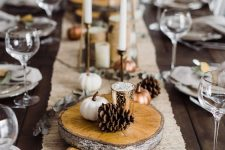 wood slices, dried eucalyptus, pinecones and mini white and copper pumpkins plus tall and thin candles are pure elegance