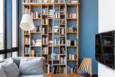 a contemporary living room with a double height bookcase and a ladder to reach all the books you may need