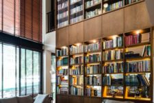 a large double-height library in the living room with additional lights and large windows plus cool sofas