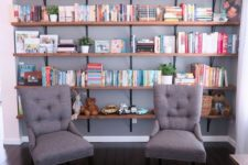 a reading nook with open shelves and a couple of comfy chairs is a cool idea for a farmhouse space like this one