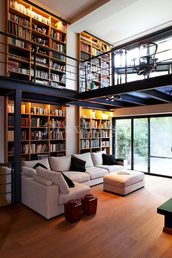 a whole two level library embracing both the living room and home office looks wow