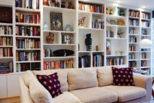 an oversized white bookcase with additional lights take the whole wall turning the living room into a library