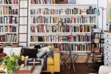 built-in open shelves and a ladder to reach the books easily create a library here in the living room