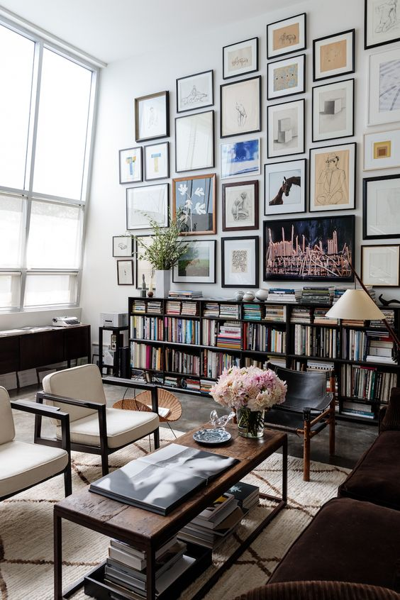 dark bookshelves and matchign dark furniture make the space stand out, and a gallery walls adds to the decor