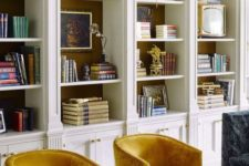 elegant and refined built-in white bookshelves with molding look bold and with bright chairs create a reading space