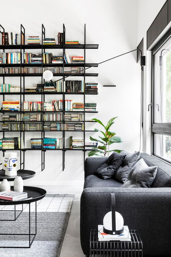 floating black open shelves and dark furniture stand out in a neutral space and enliven it