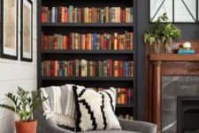 graphite grey built-in bookcases and a grey chair plus a stone fireplace to create a cozy dark reading nook