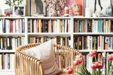 long white shelving units covering the whole wall and a wicker chair to create a cool cozy reading space