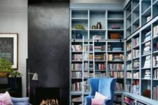 mint blue built-in bookshelves take two walls, and a refined blue velvet chair create a cozy reading nook