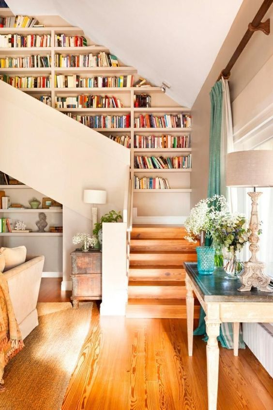 shelves built into the wall next to the staircase allow you saving space and look nice, plus stairs make it easy to reach them
