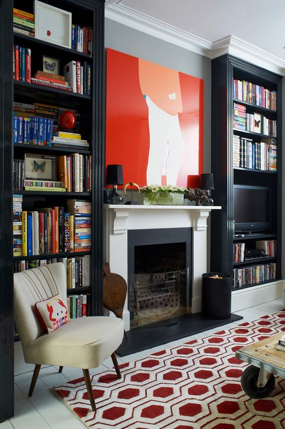 tall dark bookcases separated with a fireplace and a chair make up a nice mini library