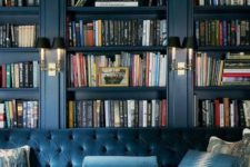 teal built-in bookcases and a matching sofa create a refined and luxurious library in the space