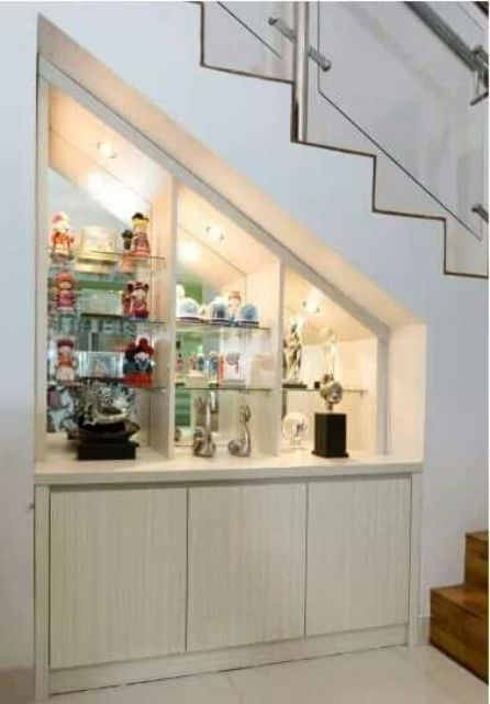 a lit up and built-in home bar right under the stairs is a cool idea that won't take any space in your home